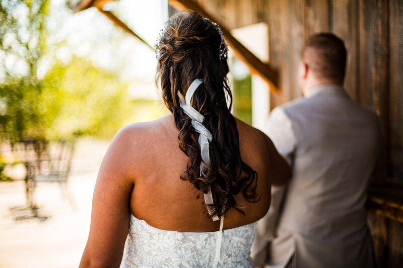 Bride reaches out to get groom's attention  during first look portraits at Port Farms