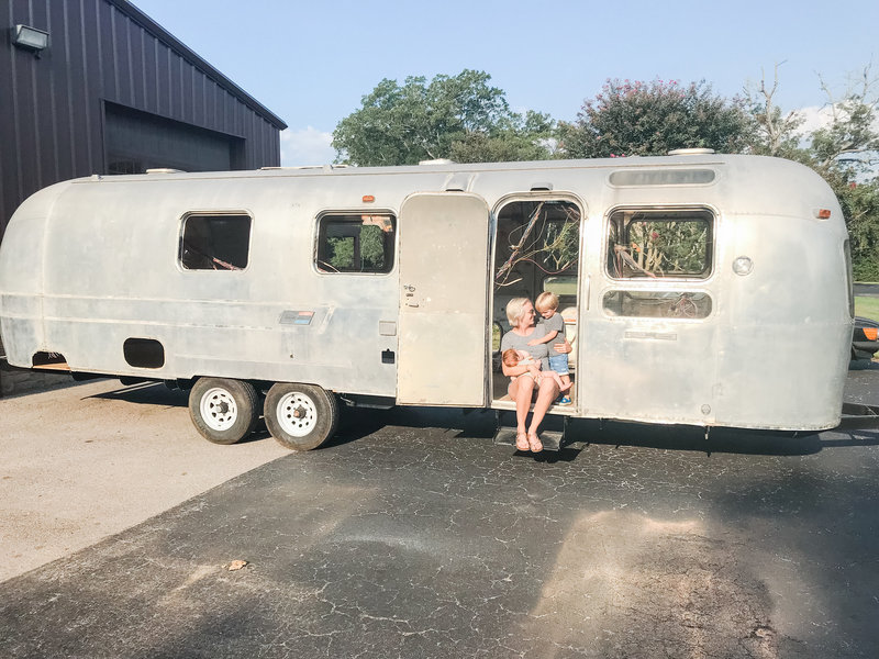 Mama sitting in doorway of gutted vintage airstream trailer, nursing baby and hugging toddler.