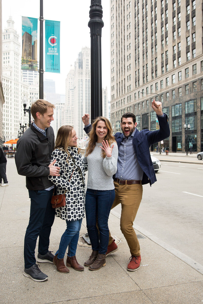 friends celebrating after surprise proposal woman gasping from surprise engagement downtown chicago mag mile