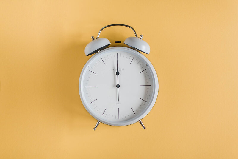 a clock against a yellow backdrop from social curator