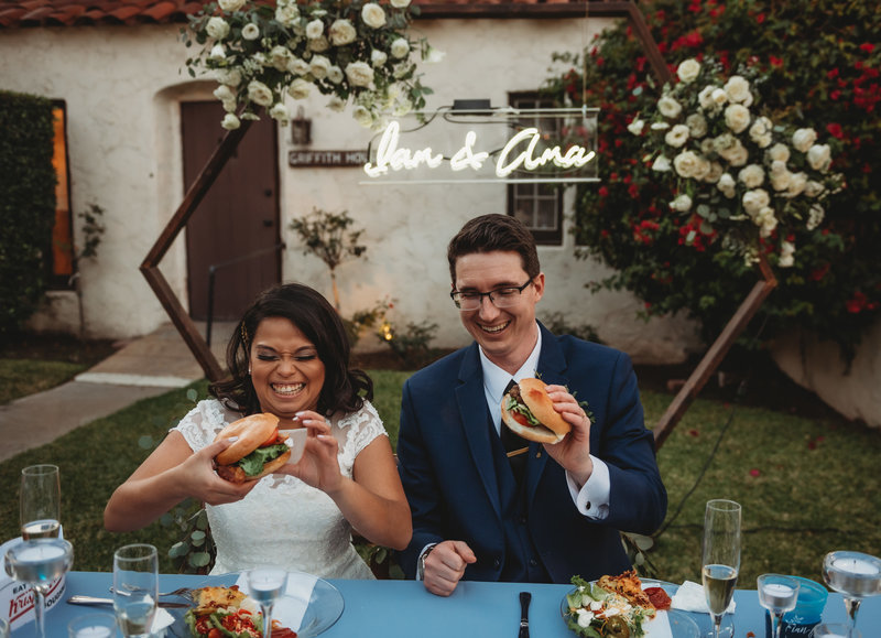 Bride and Groom eating burgers for their wedding dinner.