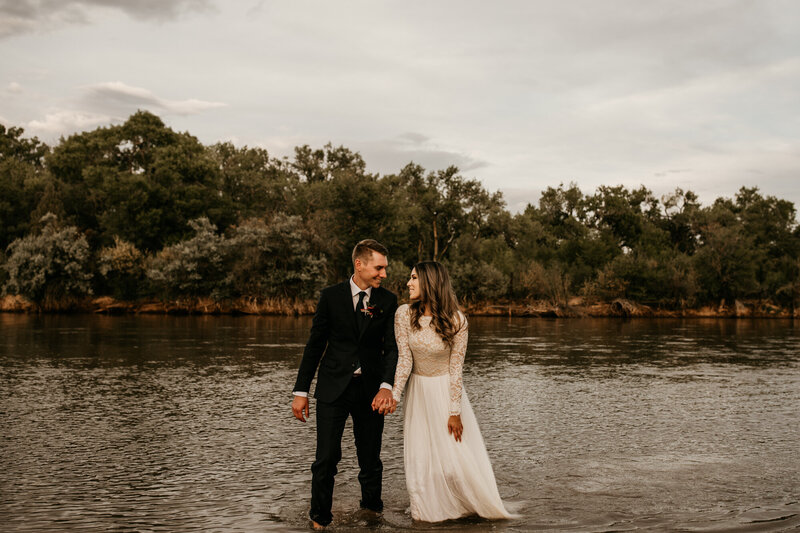 married couple walking through river in wedding dress and suit