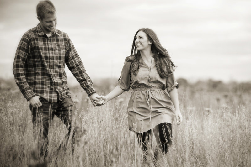 Engaged couple holding hands and walking across field of dry grass.