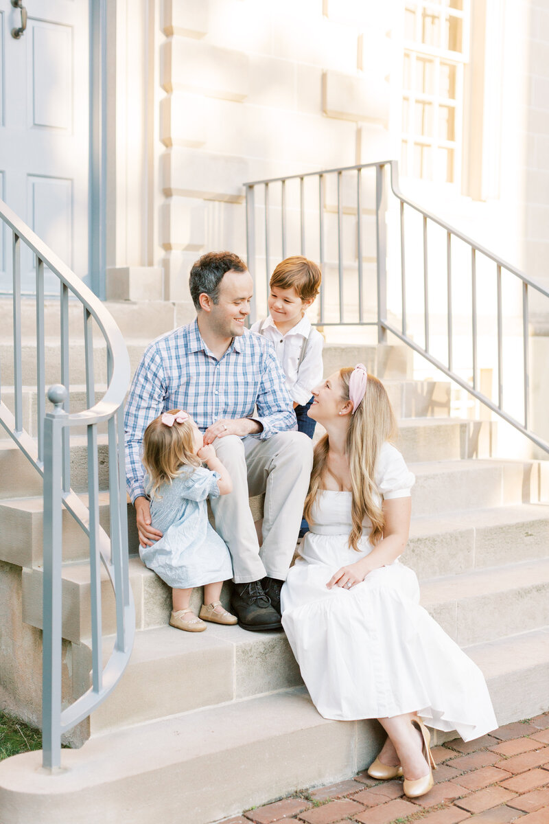 Family sitting on steps of Carlyle House during Alexandria family session.