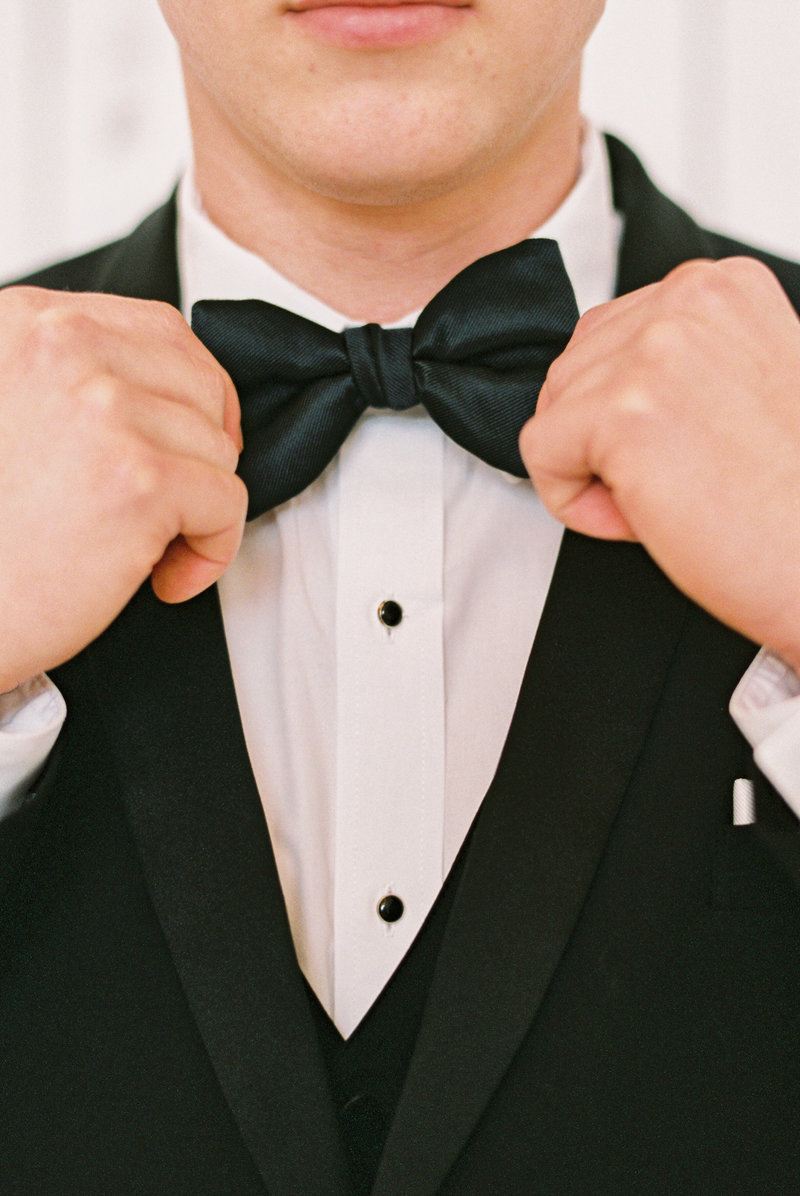 Young man in black tux adjusting his black bow tie