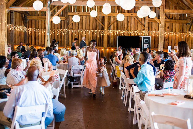 Bridesmaid walks down the aisle at a Betsy's Barn wedding