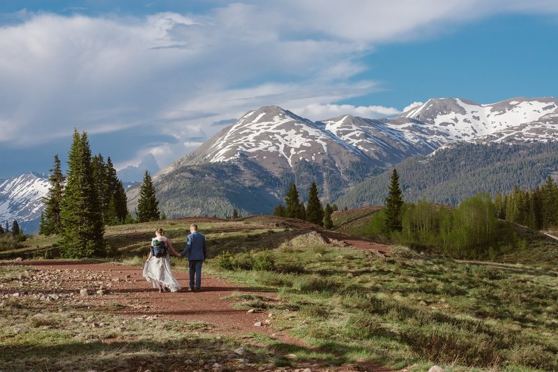 Bride and groom hike through Molas Pass in the San Juan mountains for their Silverton elopement
