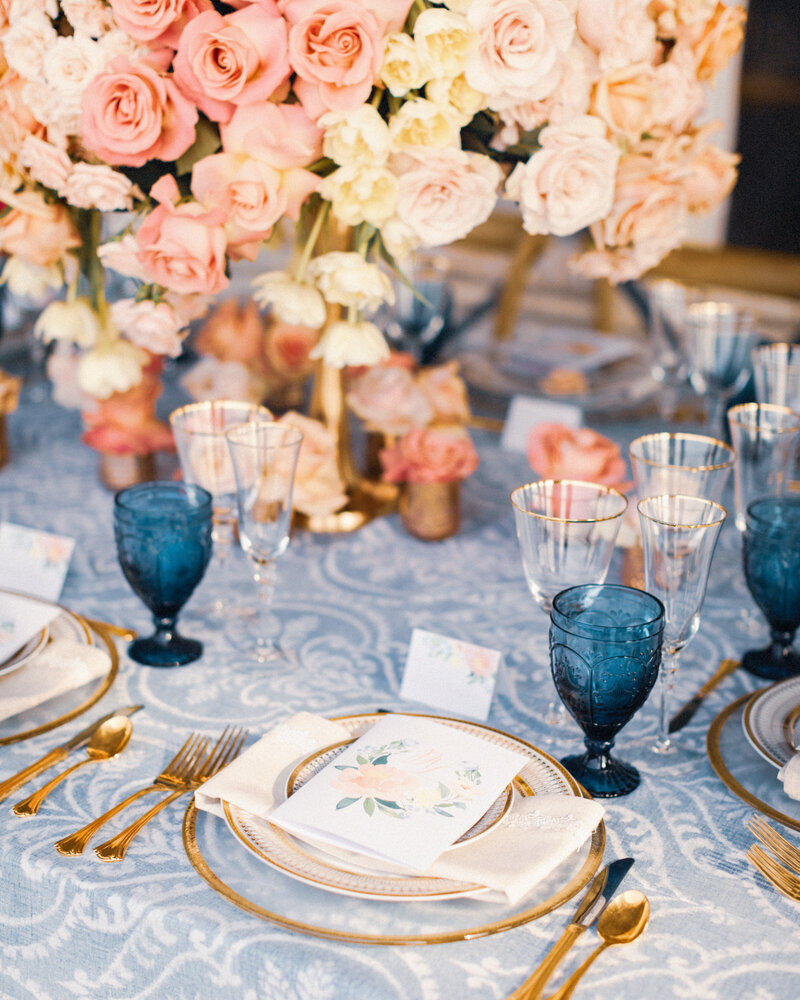 A wedding table is set with vintage lace, blue glassware, gold plates and cutlery and floral menus at a luxury wedding.