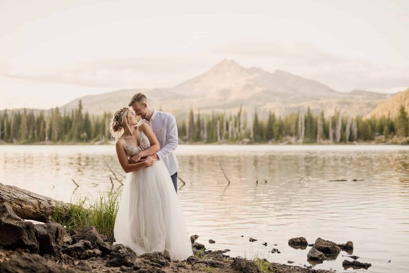 A man and woman stand in an embrace on the short of Sparks Lake.