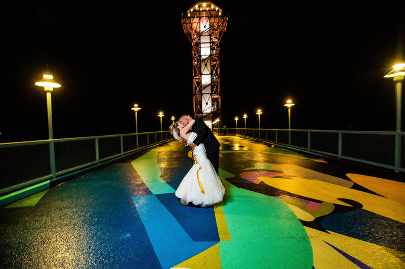 Bride and groom kissing in front of Bicentennial Tower at night