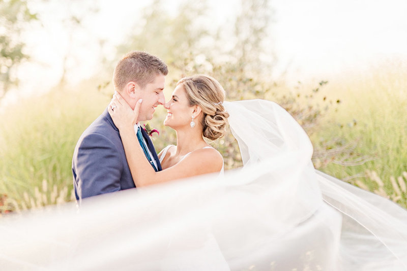 bride-and-groom-portrait-with-veil-flowing-in-the-wind