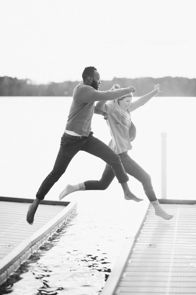 couple jumping over dock black and white