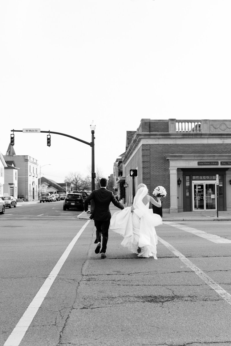 Black and white photos of a couple running across the crosswalk on their wedding day as the groom holds the dress train