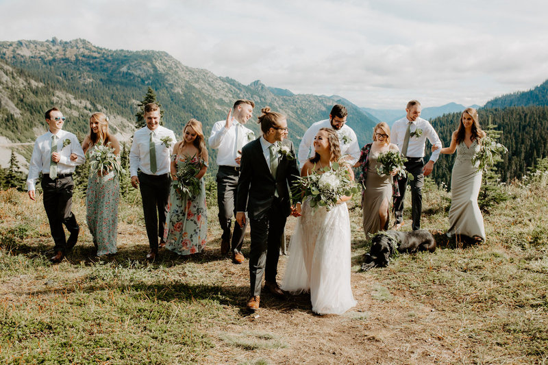 Bride and Groom with their bridal party walking and laughing together in the mountains
