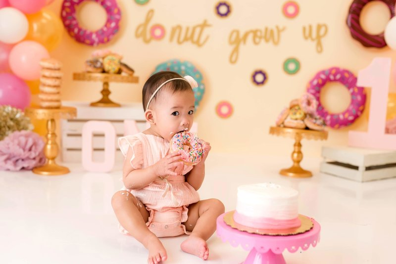 one-year old girl eating a pink donut and sitting in front of her birthday cake as part of her cake smash session