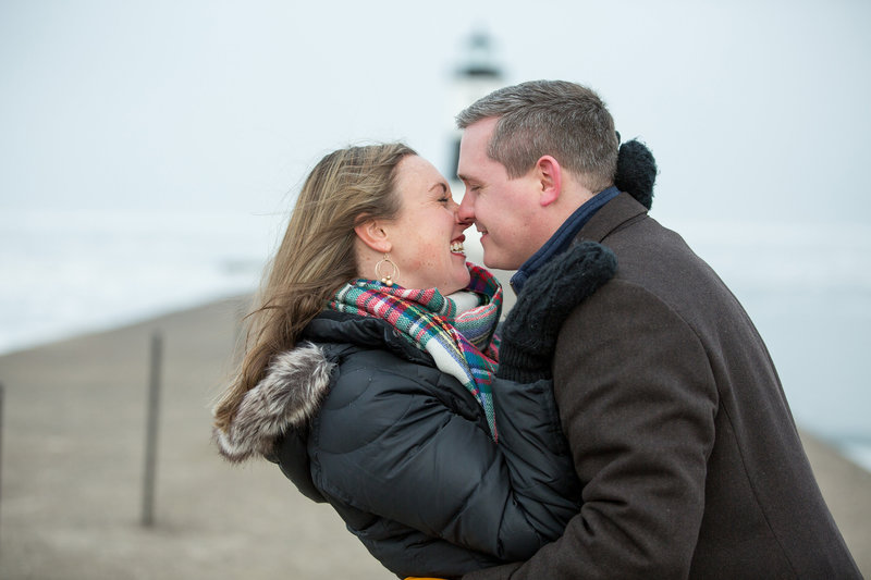 Engaged couple try to stay warm on a cold windy day at the North Pier in Erie, PA