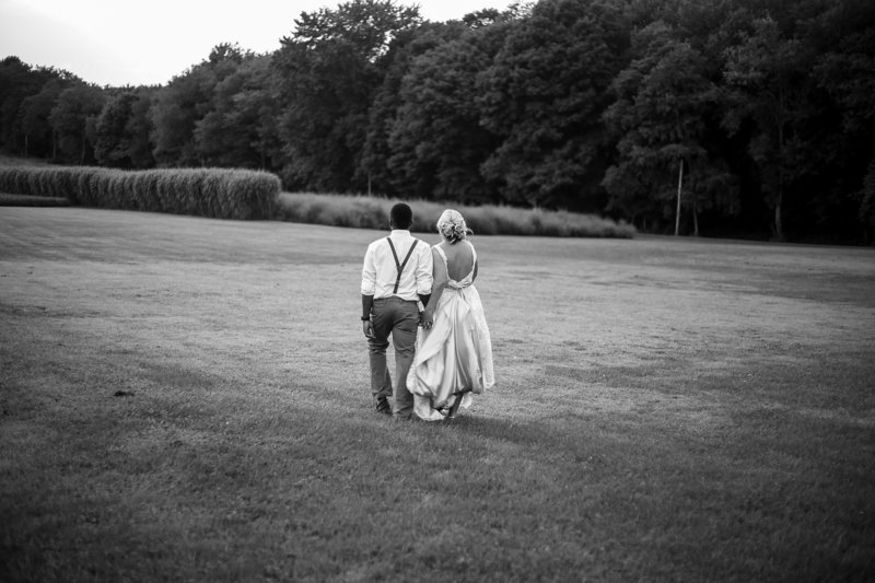 Bride and groom walk through a field at Betsy's Barn