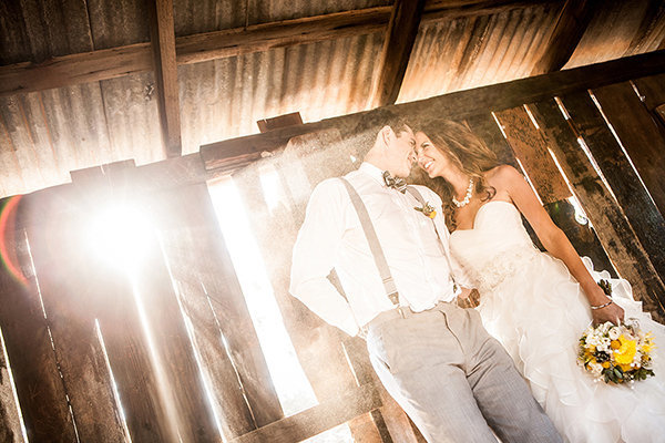 couple holding each other at a barn venue with incredible light taken by ABM Photography
