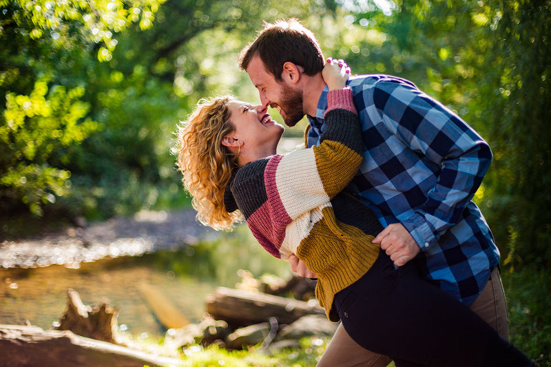 Man dips his fiancee next to Cascade Creek for engagement photos at at Frontier Park