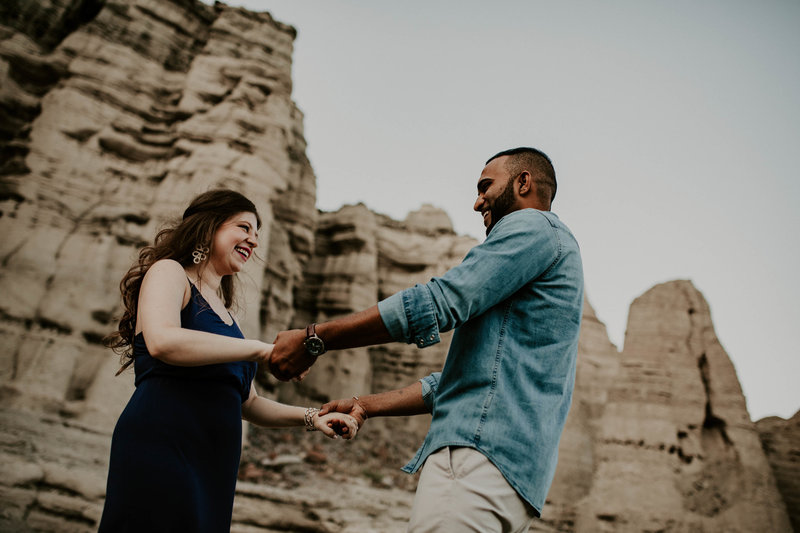 engaged couple holding hands and spinning in a canyon