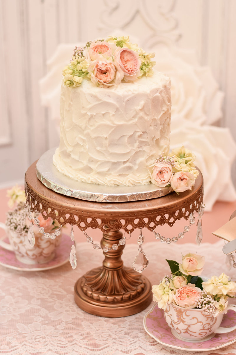 rustic wedding cake for two on a gold cake stand at the Golden Horseshoe inn wedding venue