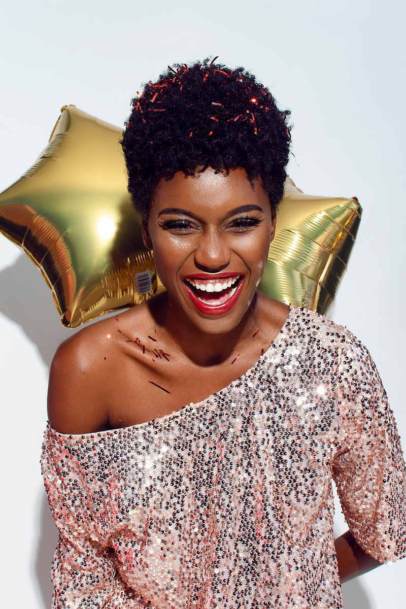 Canva - Photo of Laughing Woman with Confetti on Her Hair and Shoulders Posing In Front of White Background While Holding Golden Star Balloons Behind Her Back
