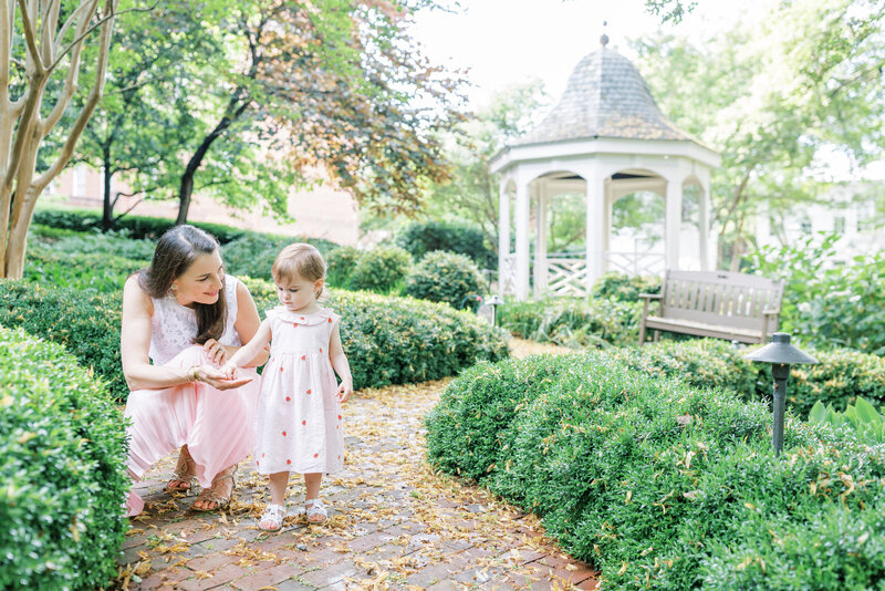 Mother kneels next to daughter at Carlyle House in Alexandria family session.