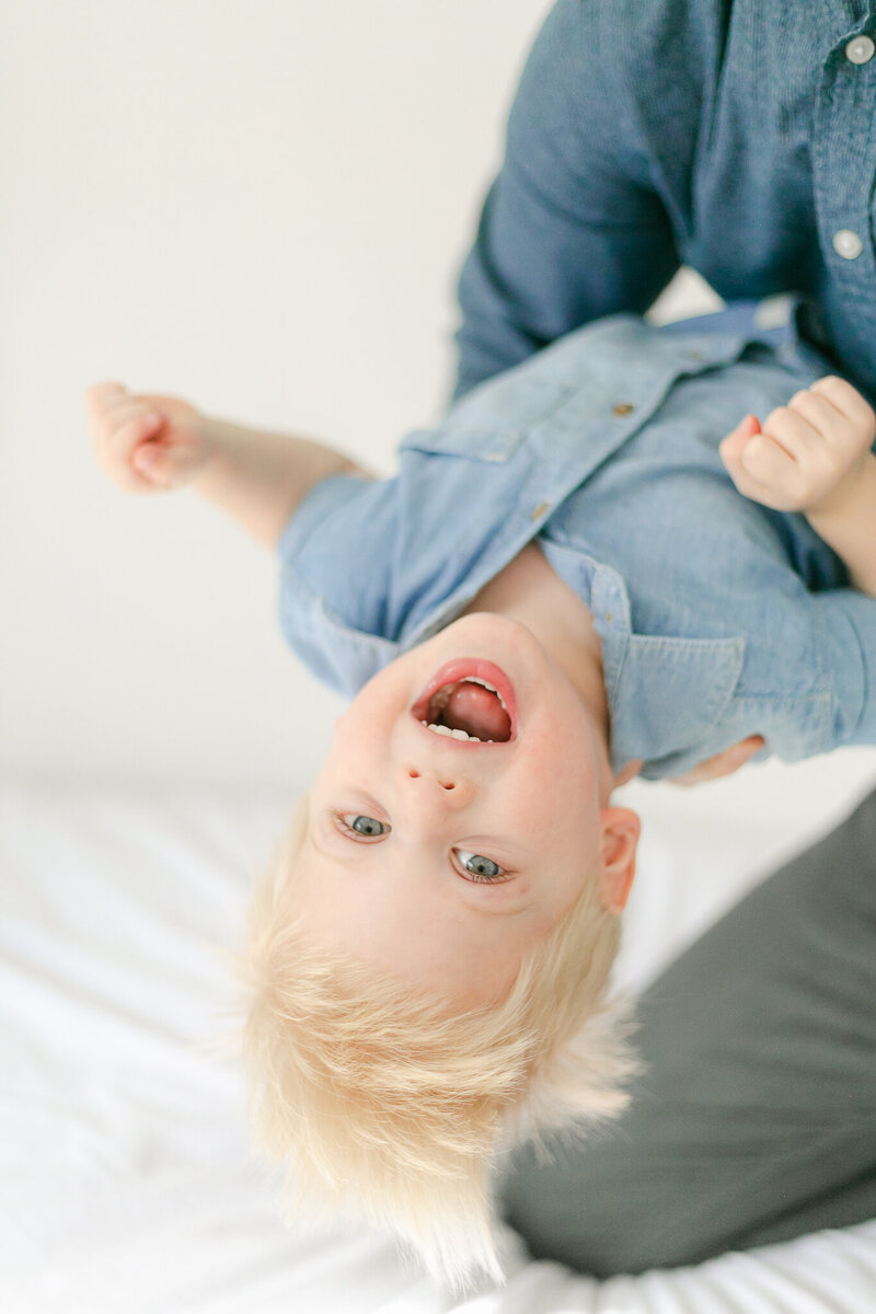 Portrait of a toddler laughing while being swung upside down by his dad during an in-home Rochester family photography session.