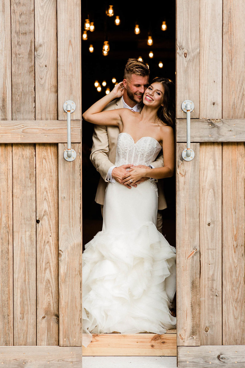 Bride and Groom between barn doors