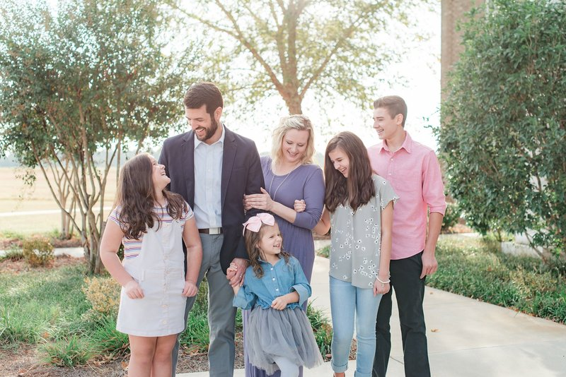 Photograph of family by Macon GA photographer Ann Steward. Family with four children laughing and smiling during photo session with Ann Steward Photography.
