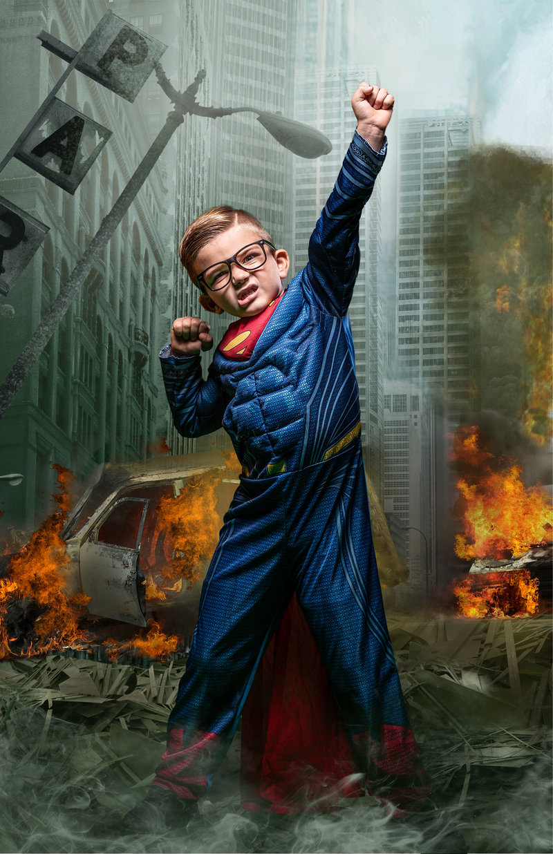 A young super hero in a Superman costume  in a post apocalyptic scene