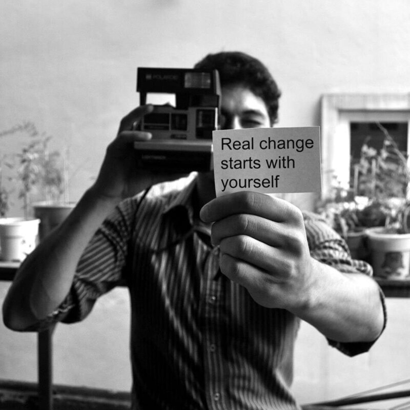 Man holding polaroid camera with note that says real change starts with yourself