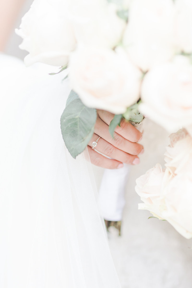 Wedding ring on bride while holding bouquet of white roses by C. elyse photos