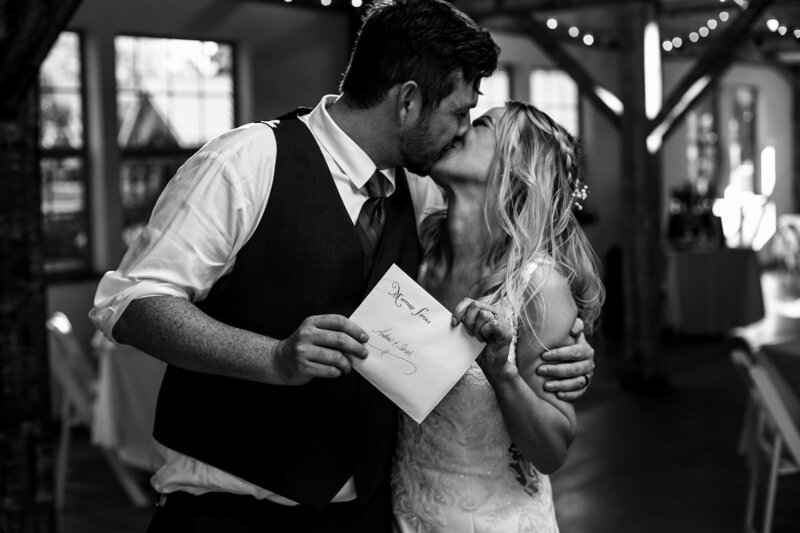 Couple kisses as they show off their marriage license at their Quincy cellars wedding