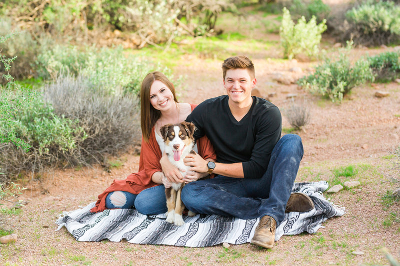Engaged Couple holding dog on mexican blanket in desert