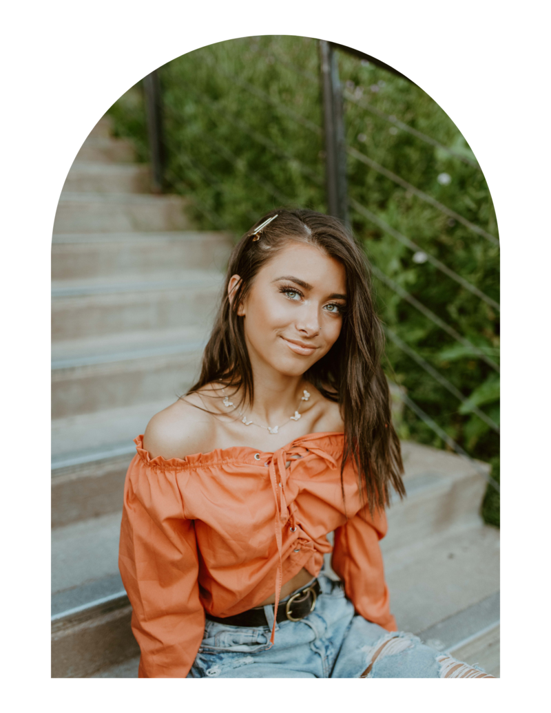senior girl sitting on steps smiling