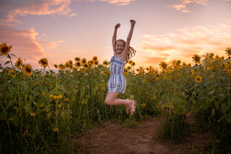 Girl jumping in Sunflower field at sunset