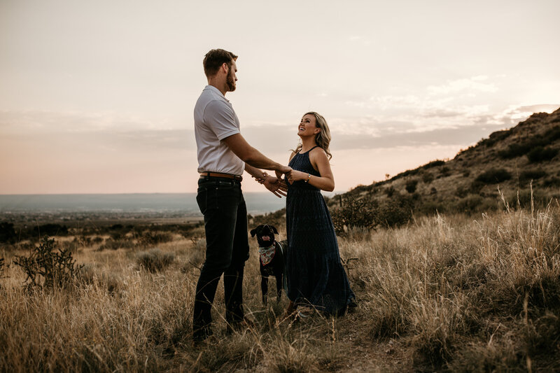 engaged couple holding hands with dog in the desert