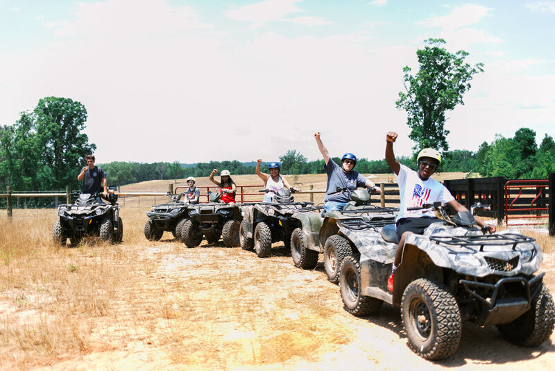 Group of John Deere four wheeler riders cheer and have fun during a unique group experience in North Georgia