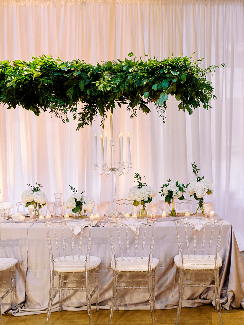 Romantic indoor wedding reception with lucite details and greenery