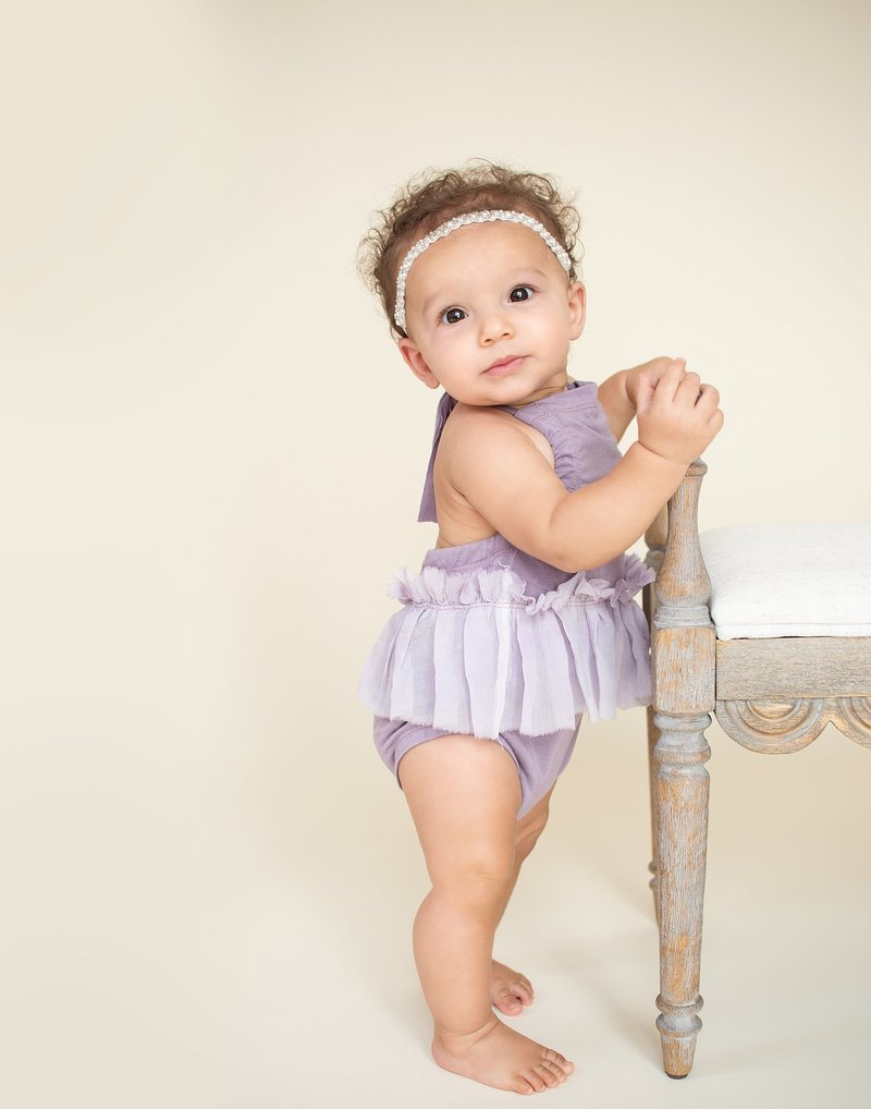Baby girl standing holding on to bench