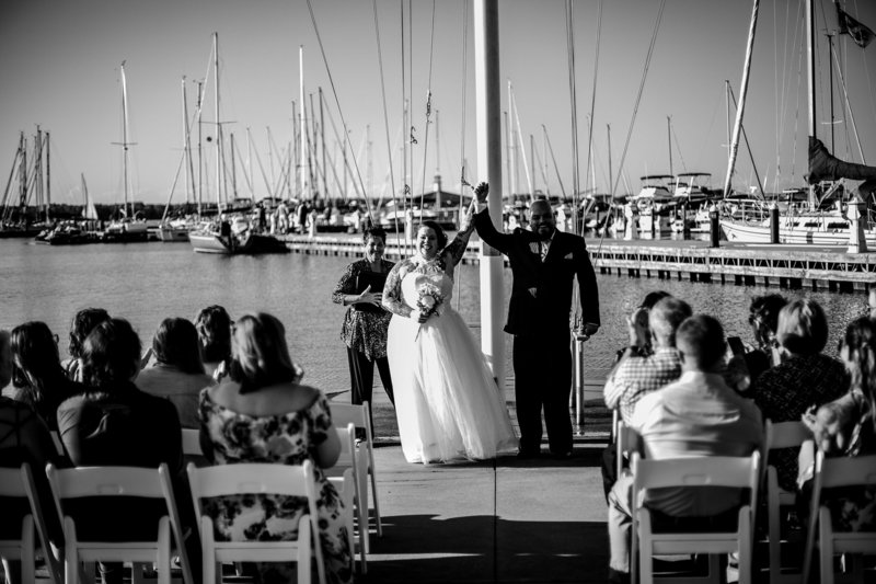 Bride and groom raise hands together at the end of their Erie Yacht Club wedding ceremony