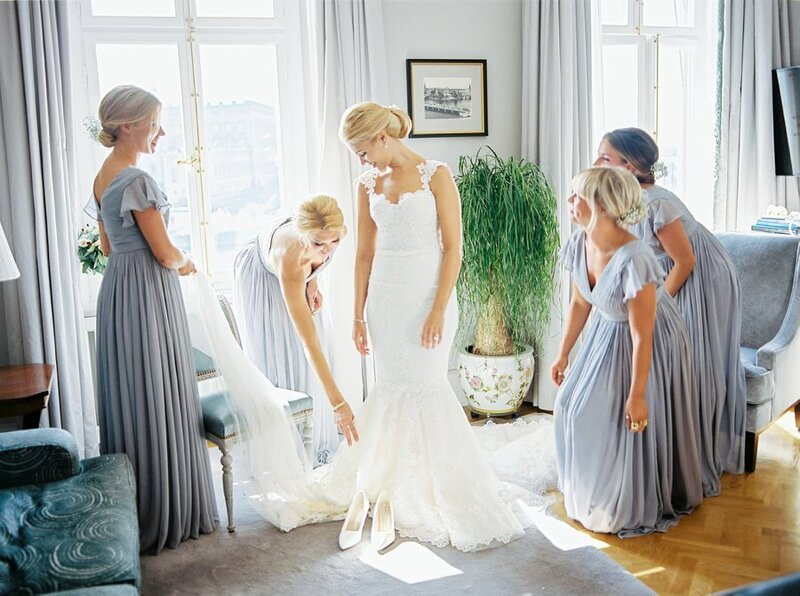 0012_Bridesmaids-helping-the-bride-put-on-her-Ida-Lanto-wedding-gown-1