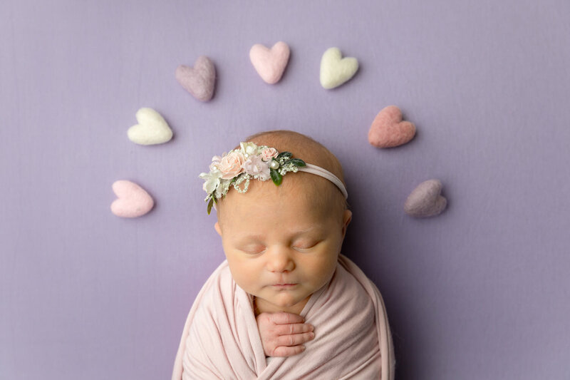 newborn girl swaddled in pink against a purple background with felted hearts