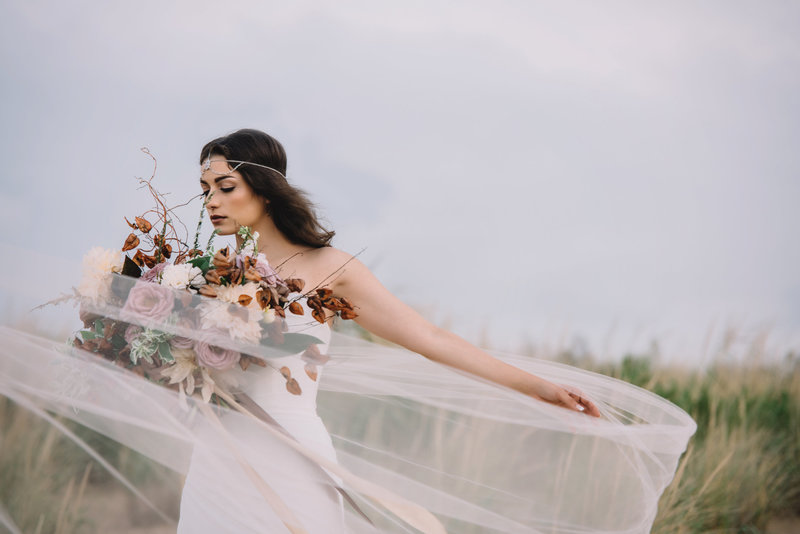 bride standing outside with veil blowing in the wind