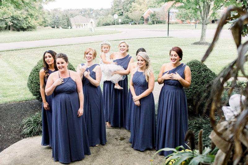 A group of bridesmaids in purple dresses turn around and see the bride in her dress and begin to cry