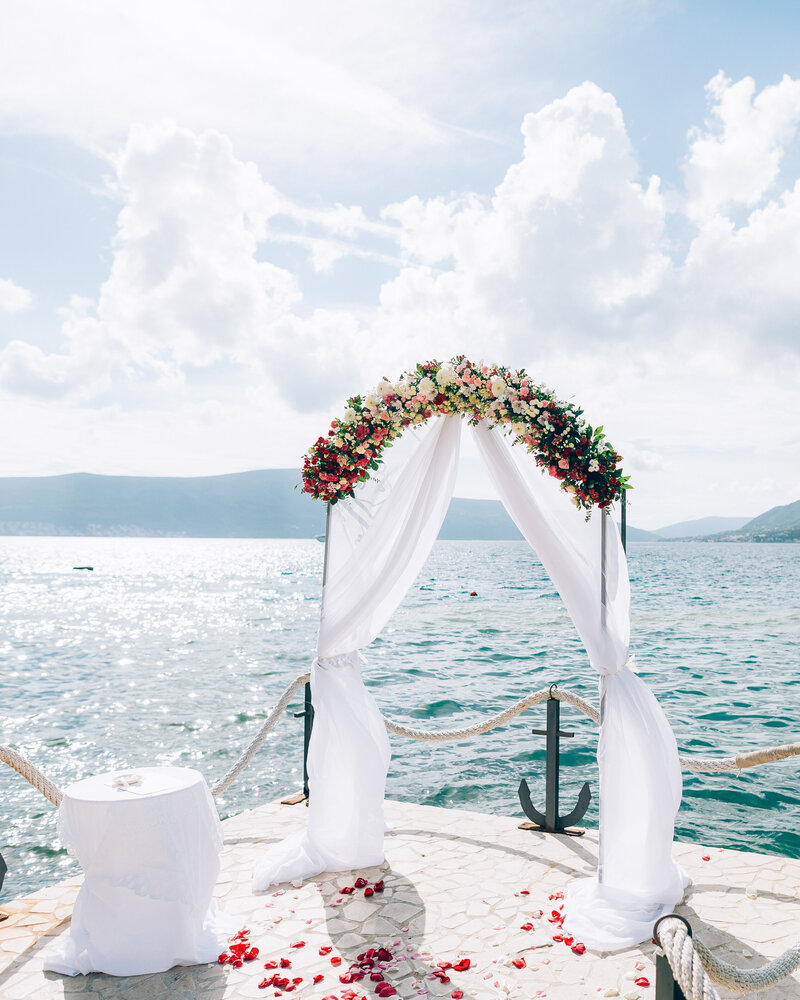 A wedding arch is set at the end of the aisle with panoramic views of the mountains and sea in Greece.