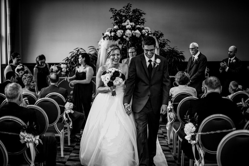 Recessional portrait of bride and groom laughing at Sheraton Erie Bayfront Hotel