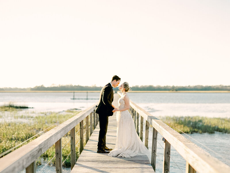 Bride and groom holding hands and kissing on wooden dock on river at Charleston Wedding