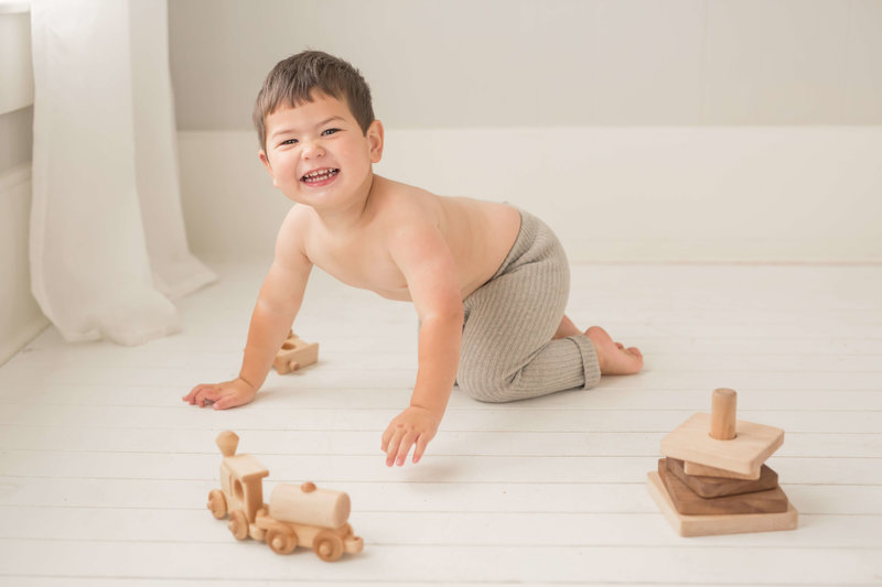 toddler playing with wooden toys in houston photography studio